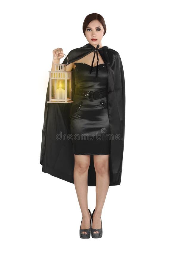 Jonge Aziatische vrouw in een heksenkostuum met de lantaarn van de mantelholding royalty-vrije stock foto's