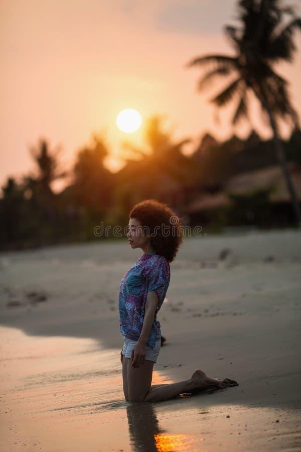 Jonge aziatische vrouw kniel op de surflijn op het zeestrand stock fotografie