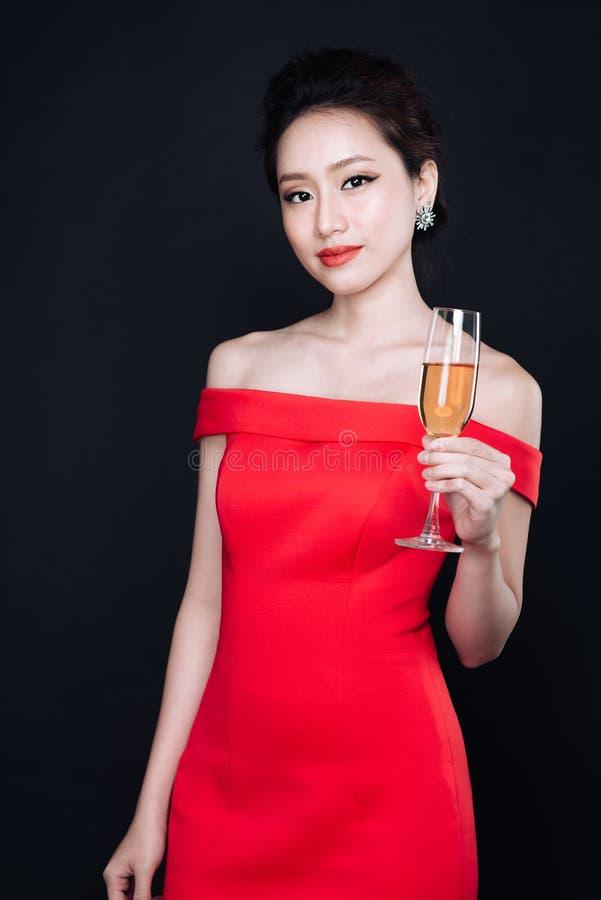 Jonge Aziatische vrouw in luxe rode kleding met glas van fonkelende wi stock afbeelding
