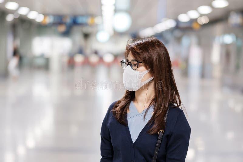 Jonge Aziatische vrouw met een beschermingsmasker tegen het Novel coronavirus of de Corona Virus Disease Covid-19 op vliegveld, i stock foto