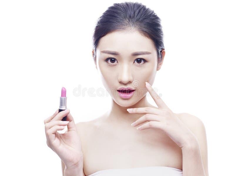 Jonge Aziatische vrouw met lippenstift stock foto's