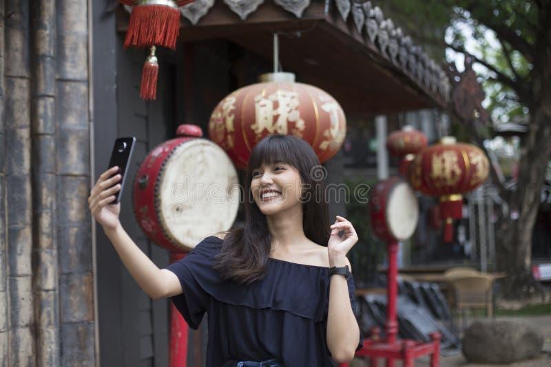 Jonge Aziatische vrouw selfie met smartphone in de stad van China stock foto's