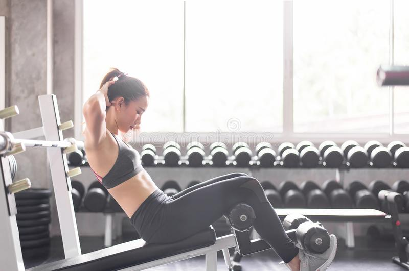 Jonge Aziatische vrouw situp of kraken die in gymnastiek, Vrouwelijke oefening spier haar maag doen stock foto's