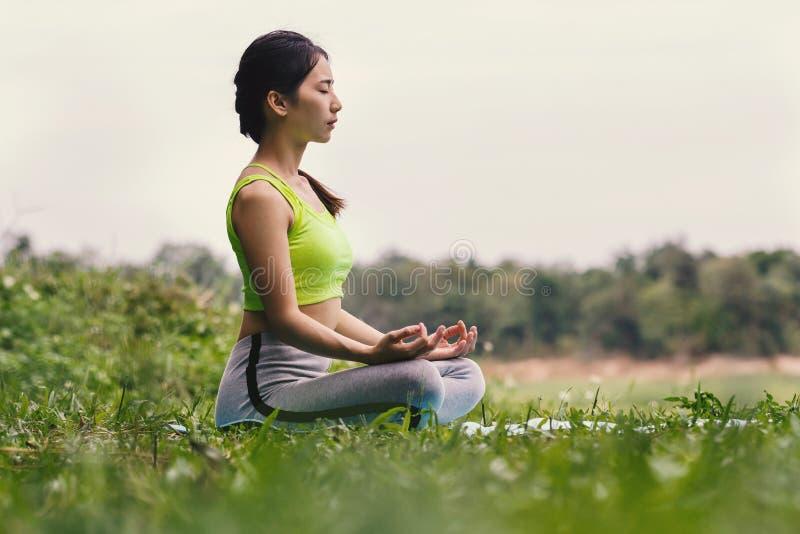 Jonge Aziatische vrouw in sportkleding die op yogamat mediteren royalty-vrije stock fotografie