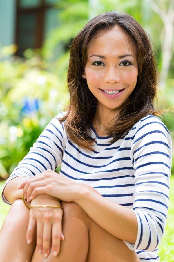 Jonge Aziatische vrouw thuis in tuinlezing stock foto
