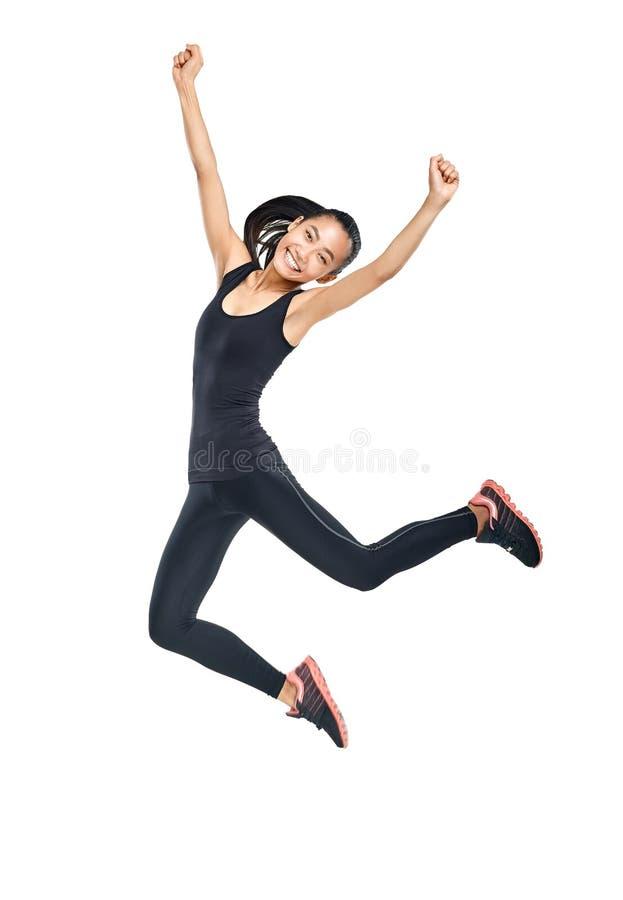 Jonge Aziatische vrouw in van sportenkleren en tennisschoenen het springen stock foto's