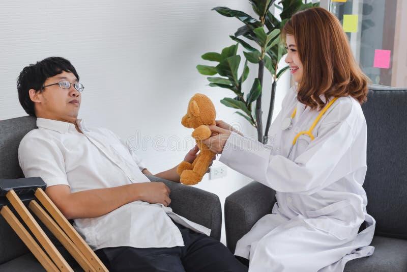 Jonge Aziatische vrouwelijke arts die bruine teddybeerpatiënt voor aanmoediging en empathie geven royalty-vrije stock afbeeldingen