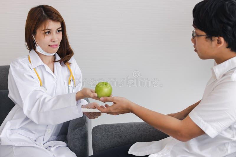 Jonge Aziatische vrouwelijke arts die groene appel geven aan patiënt voor aanmoediging en empathie royalty-vrije stock afbeelding