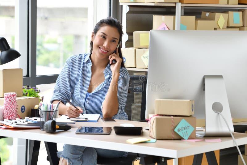 Jonge Aziatische vrouwelijke ondernemer/bedrijfseigenaar die thuis met computer werkt stock afbeeldingen
