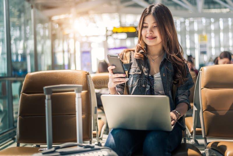 Jonge Aziatische vrouwelijke passagier die laptop en smartphone met behulp van terwijl het zitten op zetel in eindzaal en het wac stock foto