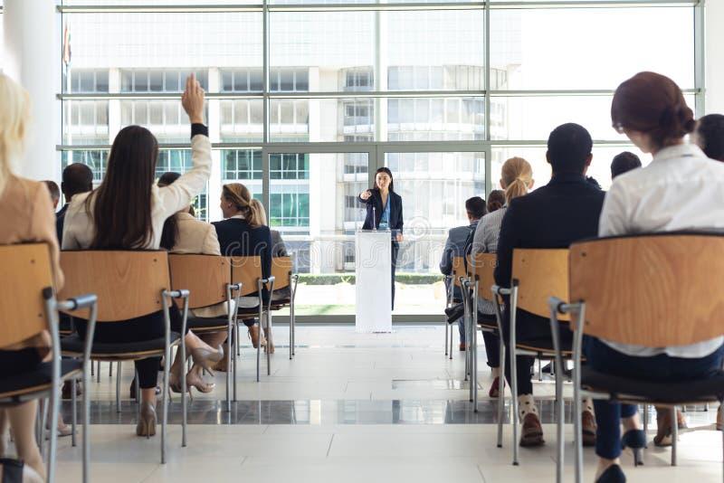 Jonge Aziatische vrouwelijke uitvoerende het doen toespraak in conferentieruimte, die vragen beantwoorden stock afbeeldingen