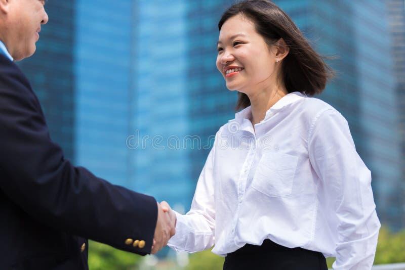Jonge Aziatische vrouwelijke uitvoerende het schudden handen met hogere Aziatische zakenman en het glimlachen stock afbeeldingen