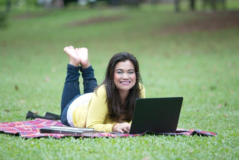 Jonge Aziatische vrouwelijke universiteit of student die op maag in park liggen stock fotografie