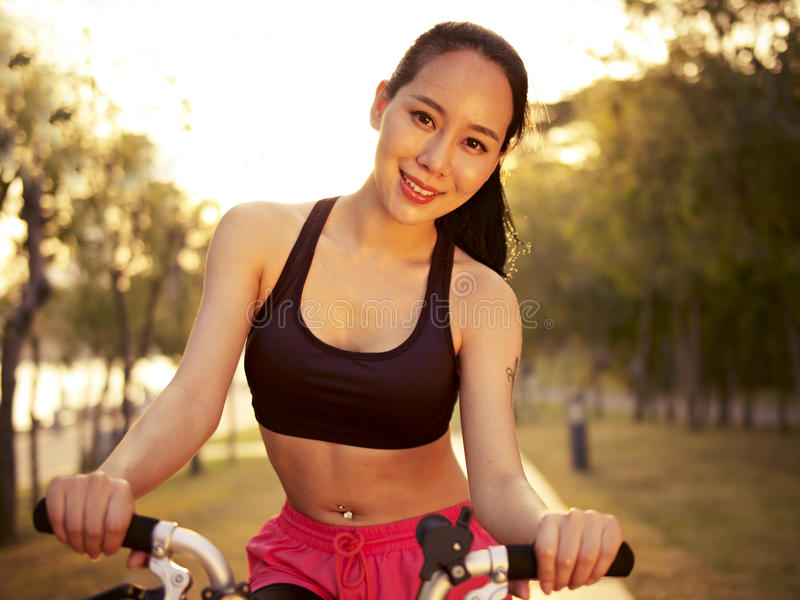 Jonge Aziatische vrouwen berijdende fiets in openlucht bij zonsondergang stock foto