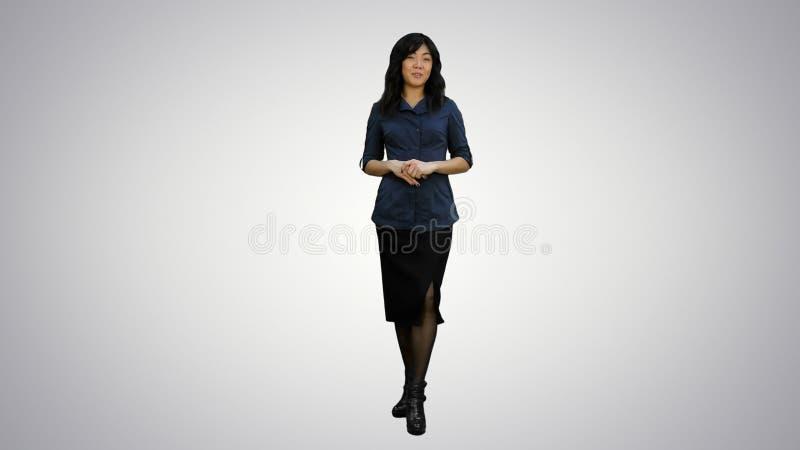 Jonge Aziatische vrouwen die en zich aan een camera op witte achtergrond bevinden spreken royalty-vrije stock foto
