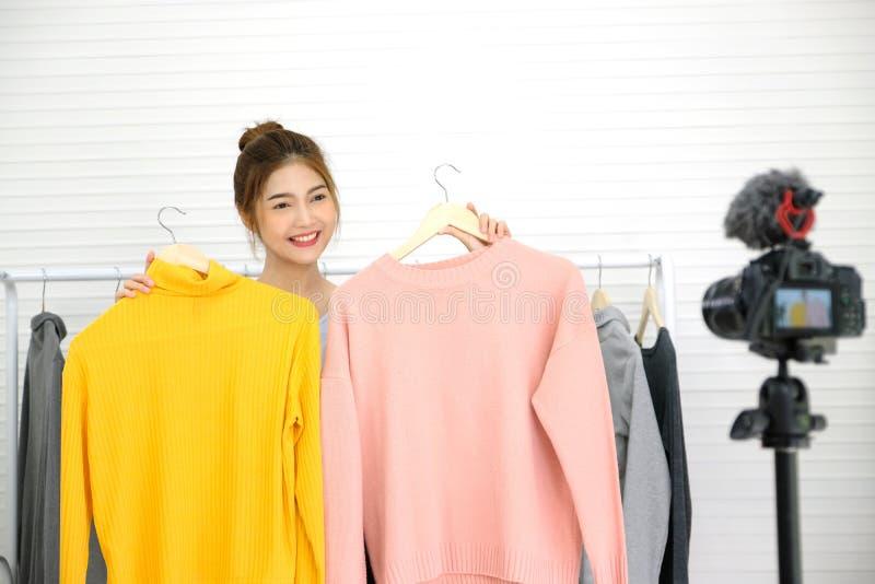Jonge Aziatische vrouwenmanier die blogger doek met het glimlachen gezicht tonen terwijl het registreren van nieuwe inhoud voor v royalty-vrije stock afbeeldingen