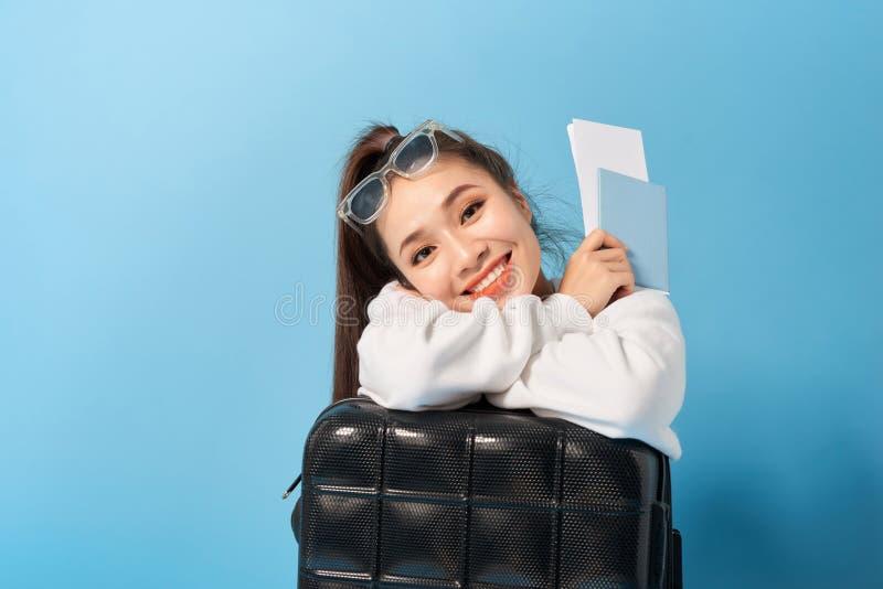 Jonge Aziatische vrouwenzitting dichtbij een paspoort van de kofferholding op een blauwe achtergrond royalty-vrije stock foto