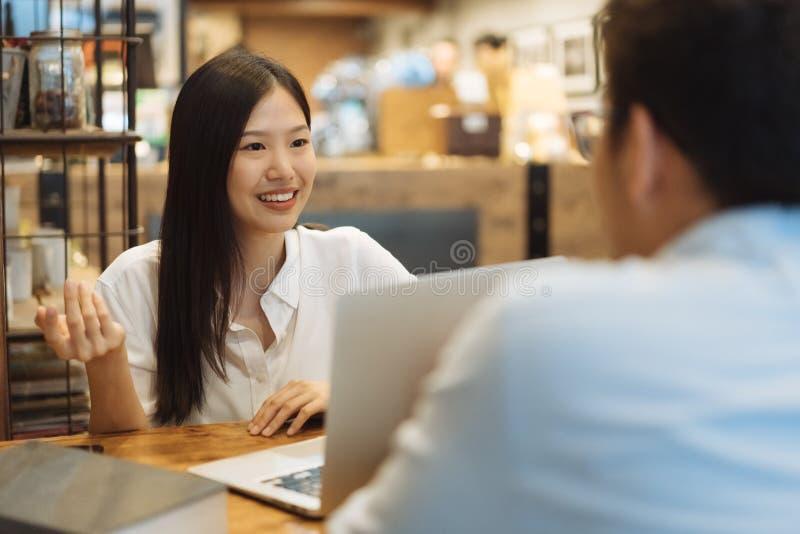 Jonge Aziatische vrouwenzitting in koffie die en een vergadering spreken hebben royalty-vrije stock foto