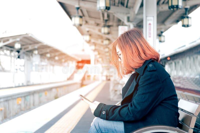 Jonge Aziatische vrouwenzitting op bank die op trein wachten en m gebruiken stock foto's