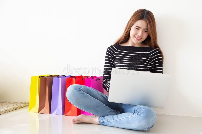 Jonge Aziatische vrouwenzitting op vloer en het winkelen online met laptop computer stock afbeeldingen