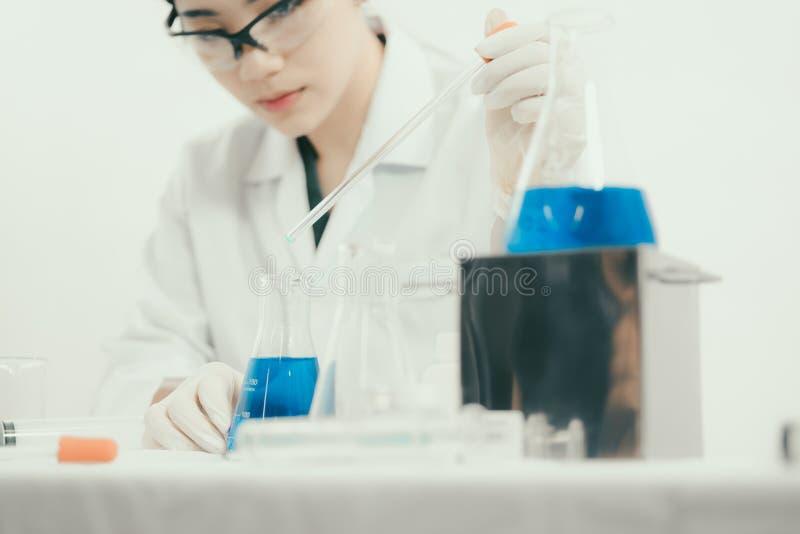Jonge Aziatische wetenschapper die in het toilet met reageerbuizen en ander materiaal werken stock afbeeldingen
