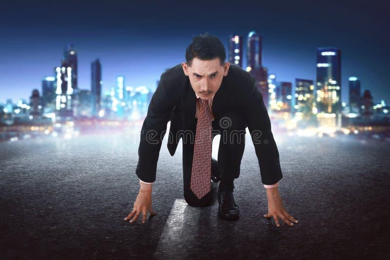 Jonge Aziatische zakenman in beginpositie klaar te rennen stock fotografie