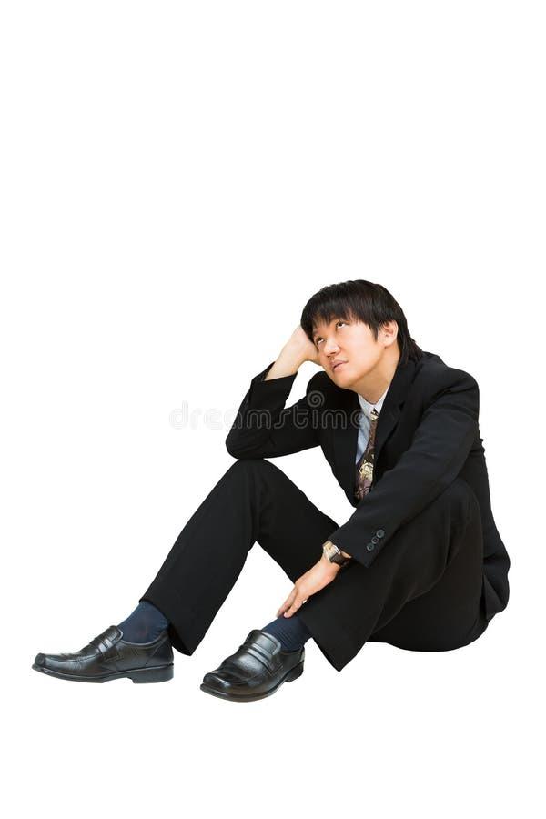 Jonge Aziatische zakenman die en omhoog boven zijn hoofd zitten kijken stock foto