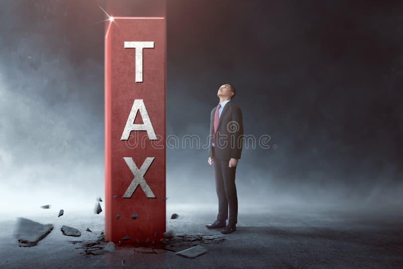 Jonge Aziatische zakenman die hoge belastingsblok bekijken royalty-vrije stock fotografie