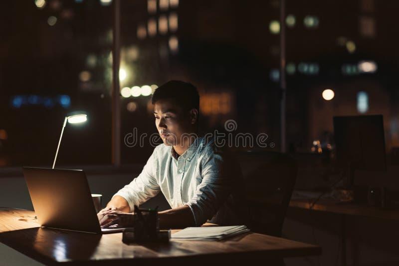 Jonge Aziatische zakenman die laat bij nacht bij zijn bureau werken royalty-vrije stock fotografie