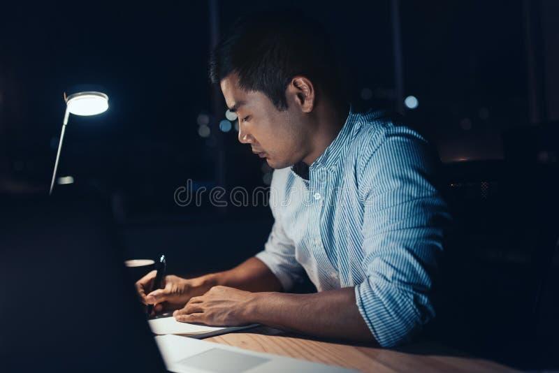 Jonge Aziatische zakenman die laat bij zijn bureau werken stock foto's