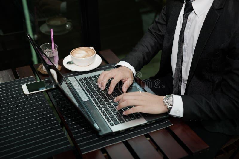 Jonge Aziatische zakenman die met laptop in een koffiewinkel werken royalty-vrije stock foto