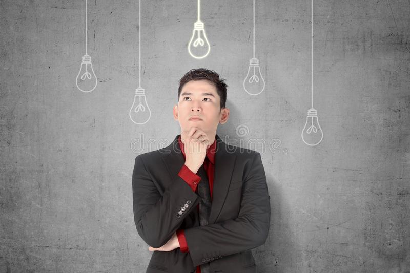 Jonge Aziatische zakenman die voor nieuw innovatief idee met het heldere gloeilampen hangen denken stock afbeeldingen