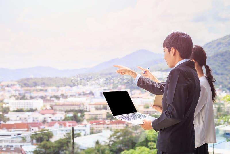 Jonge Aziatische zakenman die zich bij het terras bevinden die eruit zien te bouwen stock foto