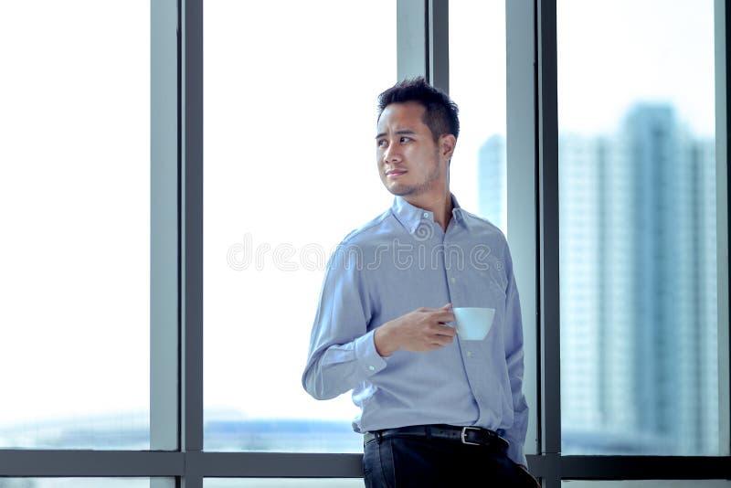 Jonge Aziatische zakenman die zich tegen die venster bevinden in zijn h wordt ontspannen royalty-vrije stock foto