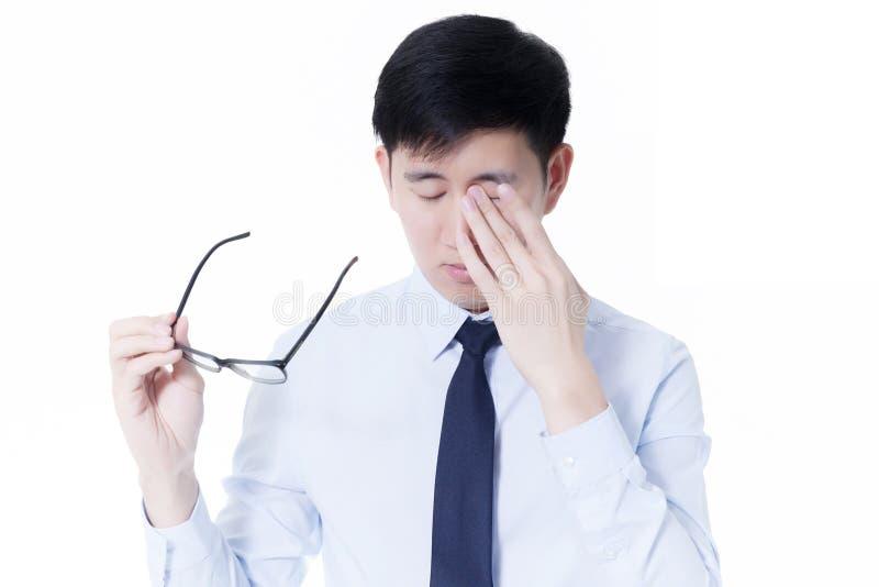 Jonge Aziatische zakenman die zijn vermoeide ogen van lange werkuren wrijven die computer met behulp van royalty-vrije stock afbeeldingen