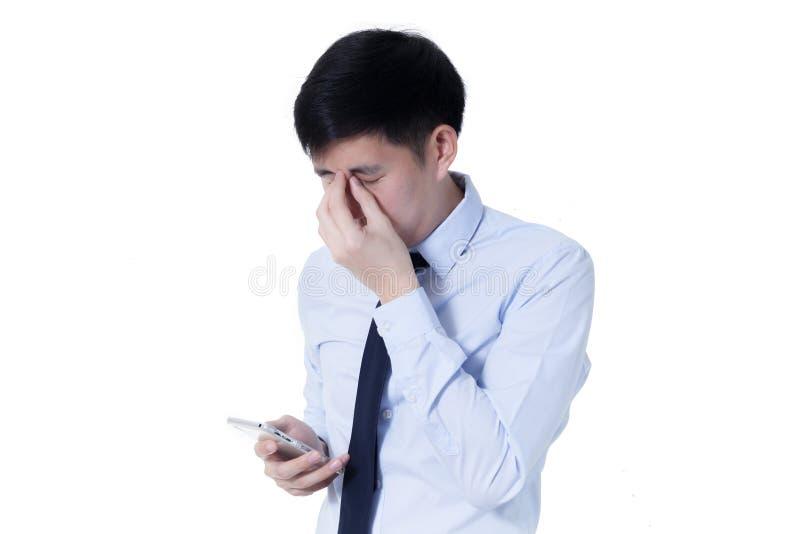 Jonge Aziatische zakenman die zijn vermoeide ogen van lange werkuren wrijven die slimme telefoon met behulp van royalty-vrije stock foto
