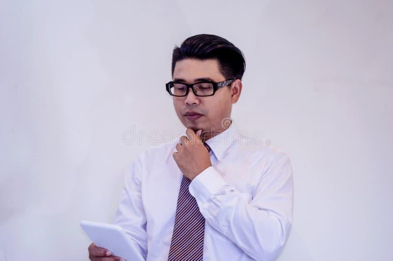 Jonge Aziatische zakenman, Meningsprogramma in het werk, online kanaal met een tablet stock afbeeldingen