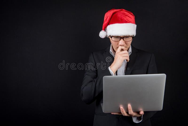 Jonge Aziatische zakenman met santahoed die laptop met behulp van royalty-vrije stock foto