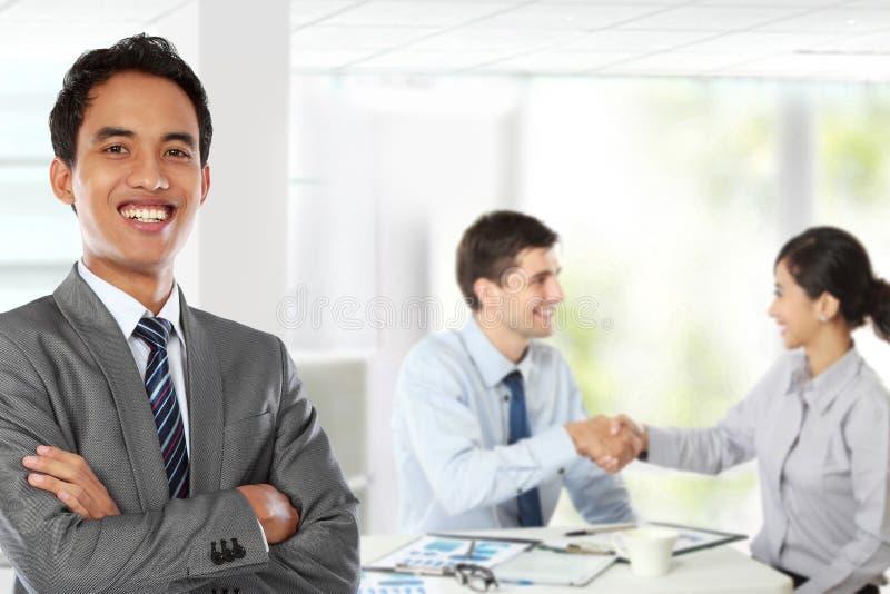 Jonge Aziatische zakenman, met zijn erachter team stock afbeeldingen