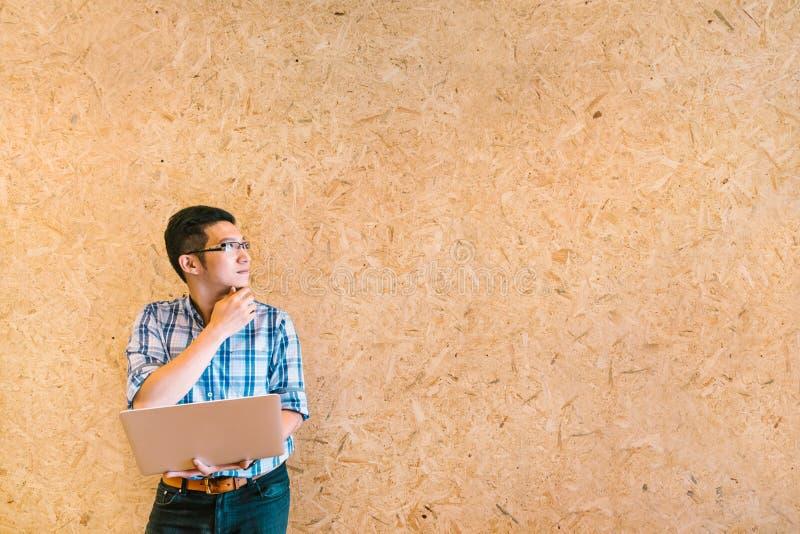 Jonge Aziatische zakenman of student met laptop die, die en exemplaarruimte denken bekijken stock afbeeldingen
