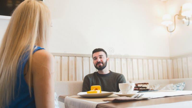 Jonge baardman en blondevrouw in een koffie royalty-vrije stock afbeeldingen