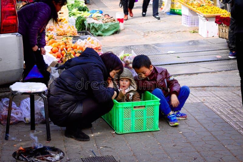 Jonge baby in de doos met zijn mum en zijn broer - Straatmarkt in Kunming stock afbeelding