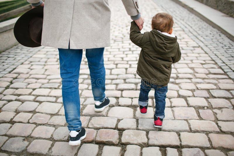 Jonge babyzoon die maatregelen met vader in openlucht treffen royalty-vrije stock afbeeldingen
