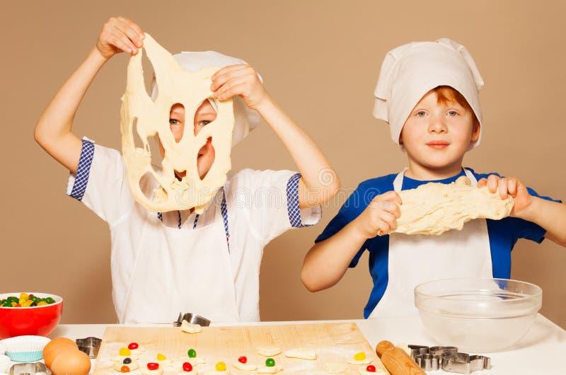 Jonge bakkers die pret het kneden deeg voor koekjes hebben stock fotografie