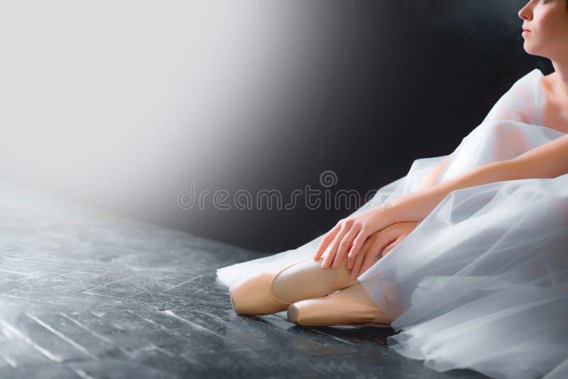 Jonge ballerina, close-up op benen en schoenen, die in pointe zitten shooses royalty-vrije stock afbeelding