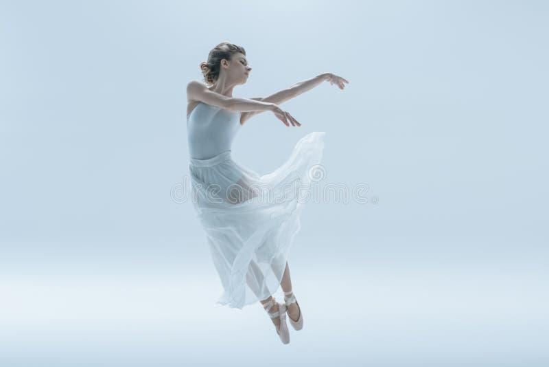 jonge ballerina die in witte kleding in studio springen royalty-vrije stock fotografie