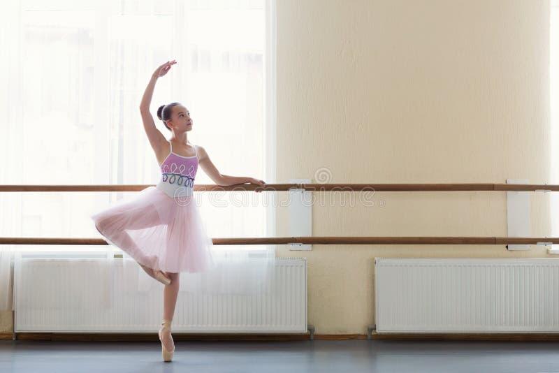 Jonge ballerina die zich op poite bij staaf in balletklasse bevinden stock foto's