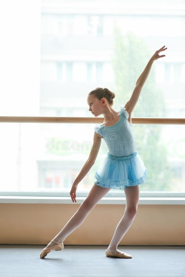 Jonge ballerina in het blauwe kleding praktizeren in studio stock foto's