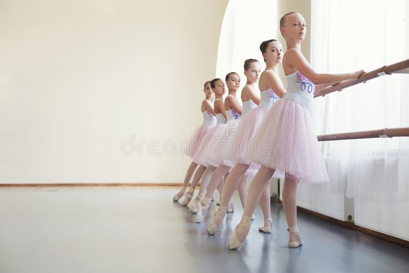 Jonge ballerina's die in balletklasse repeteren, die verschillende oefeningen uitvoeren royalty-vrije stock afbeelding