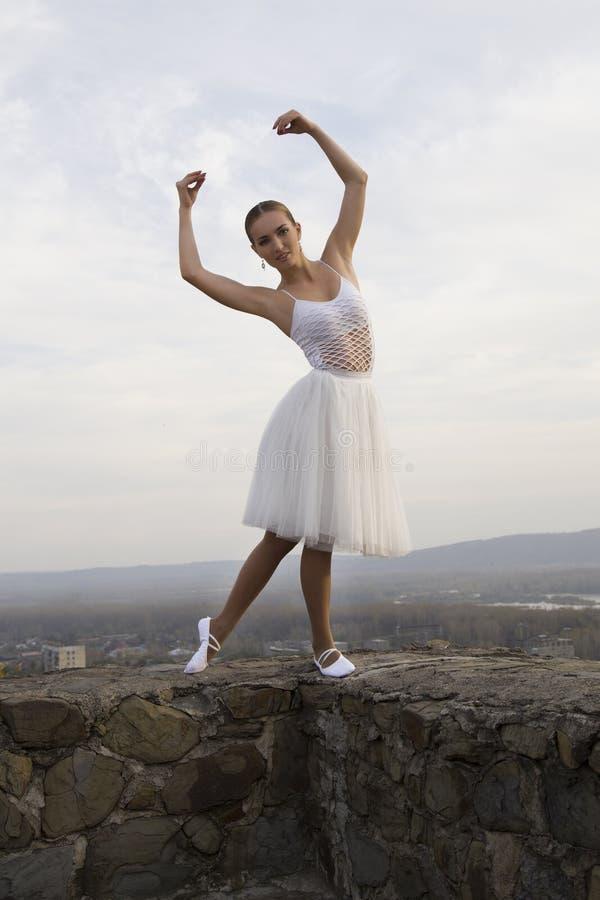 Jonge ballerina in witte kleding en satijnballetschoenen die op de rand van oude vestingsmuur stellen op een grijze hemelachtergr royalty-vrije stock foto